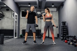 Fitness couple doing arm exercises together and lifting dumbbells indoor modern gym. Front view of a couple dressed in sportswear doing arm exercises and they make eye contact to support each other