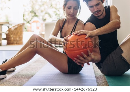 Fitness couple doing exercises with a medicine ball at home. Couple sitting back to back on a yoga mat  exercising by passing the ball to each other.