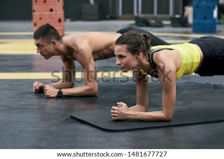 Fitness couple doing plank exercise workout in outdoors gym. Sport people exercising, planking together on street