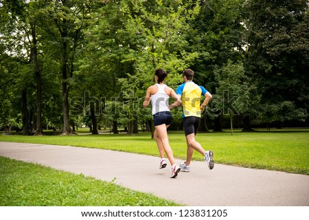 Fitness couple - young man and woman jogging in nature - rear view