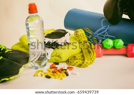 Fitness equipment and pills on white background