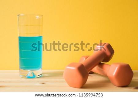 Fitness equipment dumbbells and sport energy drink on wooden table (healthy lifestyle sport object)