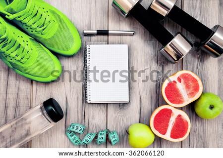 Shutterstock Fitness equipment. Healthy food. Sneakers, water,apple  on wooden background
