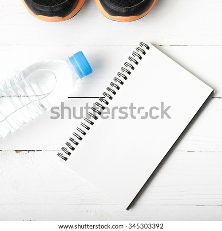fitness equipment : running shoes,drinking water and notebook on white wood table #345303392