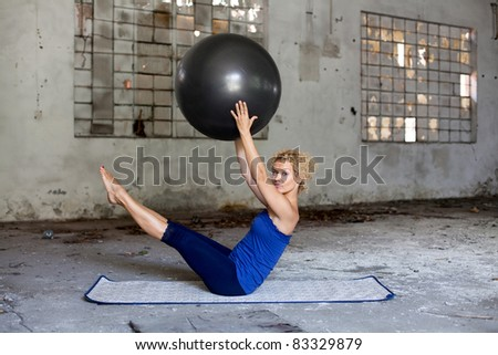 Fitness exercise / Beautiful blond woman exercises with a fitness ball in an abandoned house