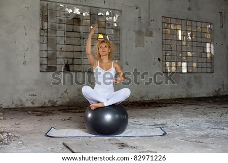 Fitness exercise / Beautiful blond woman on a grey exercise ball practicing in an abandoned house