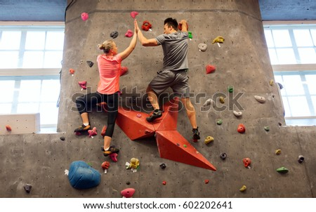 fitness, extreme sport, bouldering, people and healthy lifestyle concept - man and woman exercising at indoor climbing gym and making high five gesture #602202641