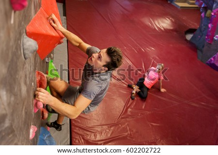 fitness, extreme sport, bouldering, people and healthy lifestyle concept - man and woman exercising at indoor climbing gym #602202722