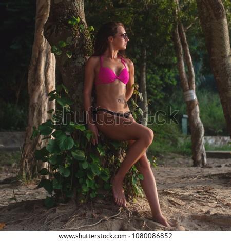 Fitness female brunette model wearing bikini and sunglasses leaning against tree holding her hair back on beach #1080086852