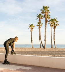 Fitness female tying the laces of roller skates before training outdoors.Active sports lifestyle concept, on beach with palm trees background with copy space.