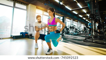 Fitness flexible girl doing leg stretching with rope from top and help from a personal trainer in the gym. Stock foto ©