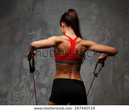 Fitness foman from back doing exercises with expander. #287460518