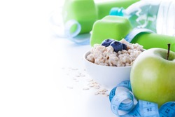 Fitness frame with energy breakfast, oatmeal, apple and mineral water with sport tools on background. Healthy weight loss concept with copy space.