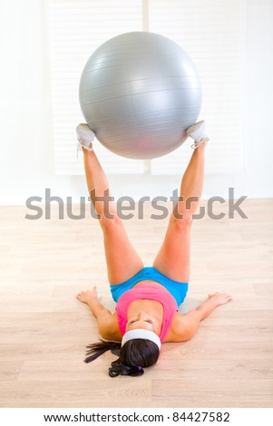 Fitness girl doing exercises with fitness ball at home
