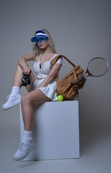 Fitness girl in white sportswear poses sitting on white box in studio holding photocamera and looking at camera.