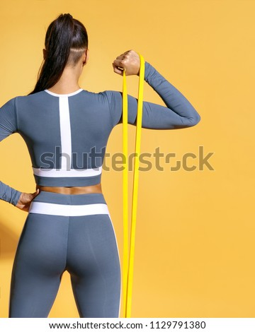 Fitness girl performs exercises for the muscles of the hands with resistance band. Photo of latin girl in fashionable sportswear on yellow background. Strength and motivation. Rear view #1129791380