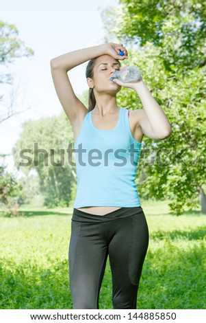 Fitness girl refreshment drinking water in the park.