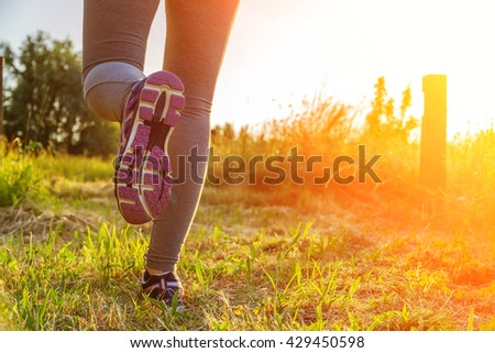Fitness Girl running at sunset in a path surrounded by fields with colorful outfit #429450598