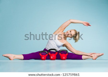 Fitness girl stretching and the kettlebells front of her, vertical format - stock photo