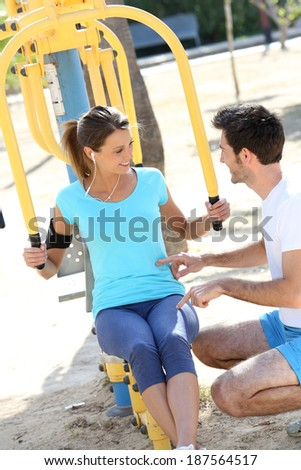 Fitness girl training with help of sports coach