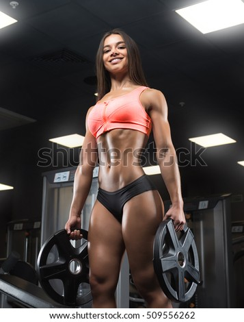 Fitness girl with a beautiful smile posing in the gym