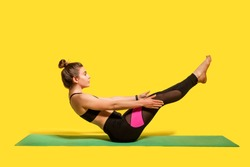 Fitness girl with hair bun in tight sportswear doing sport, physical training on gym mat, reaching hands to feet, exercising abdominal muscles, warming up. studio shot isolated on yellow background