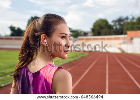 Fitness girl with sport in-ear wireless headphones. Asian female athlete woman runner wearing earphones with wing tip design for sports activities. Portrait closeup.