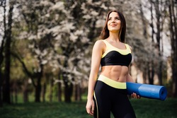 Fitness Girl with Yoga Mat Standing Outdoor in Nature - Fit woman with exercise accessory in summertime landscape