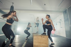 Fitness group of  strong women having cross-functional training in the gym