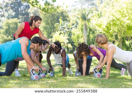 Fitness group planking in park with coach on a sunny day