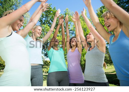 Fitness group putting hands together on a sunny day #256123927