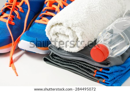 Fitness gym accessories with sport clothing, towel, drinking water and running shoes