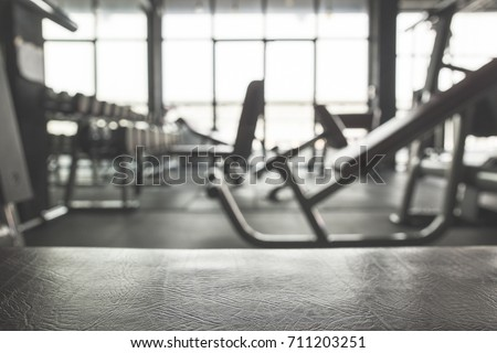 Fitness Gym background.Focus on the Bench and blurred Gym equipment
