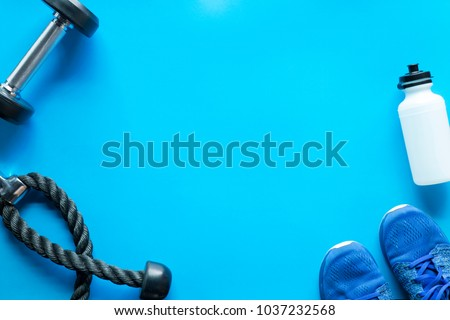 Fitness Gym equipment on blue background with free copy space
