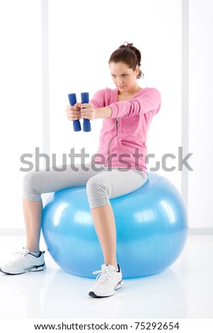 Fitness happy woman exercise dumbbell ball on white