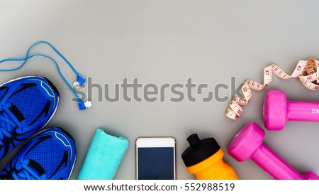 Fitness, healthy and active lifestyles Concept, dumbbells, sport shoes, bottle of waters, smartphone with headphone on grey background. copy space for text. Top view #552988519