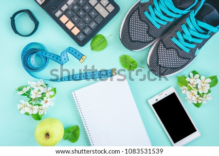 Stock Photo Fitness, healthy and active lifestyles concept. Sport shoes, smartphone, tape, calculator, fitness bracelet, flowers and green apple on green or blue background with copy space. Top view