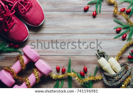 Shutterstock Fitness, healthy and active lifestyles greeting card concept, dumbbell, sport shoes, skipping rope or jump rope with Christmas decoration on wood background Merry Christmas and Happy new year concept.