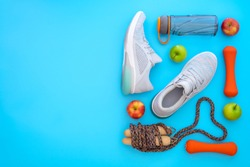 Fitness, healthy and active lifestyles love concept, dumbbells, sport shoes, bottle of waters, apples, and jump rope in heart shape on light blue background. Top view with copy space.