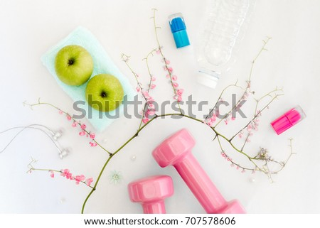 Stock Photo Fitness, healthy and beauty lifestyle concept, dumbbells, cosmetics, green apples, earphones, bottle of water and flowers on white background