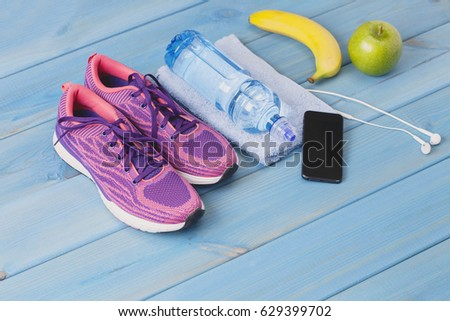 fitness healthy concept shoes applewater and smart phone on wooden background #629399702
