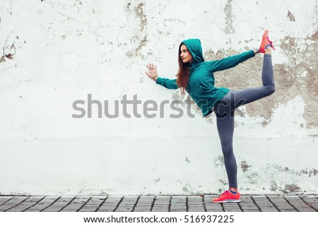 Fitness hipster girl in fashion sportswear doing yoga fitness exercise in the street, outdoor sports, urban style