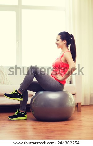fitness, home and diet concept - smiling girl exercising with fitness ball at home