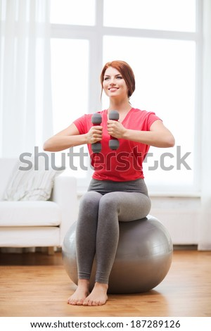 fitness, home and diet concept - smiling redhead girl exercising with fitness ball and dumbbells at home