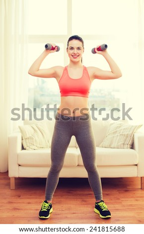 fitness, home and diet concept - smiling redhead girl exercising with heavy dumbbells at home