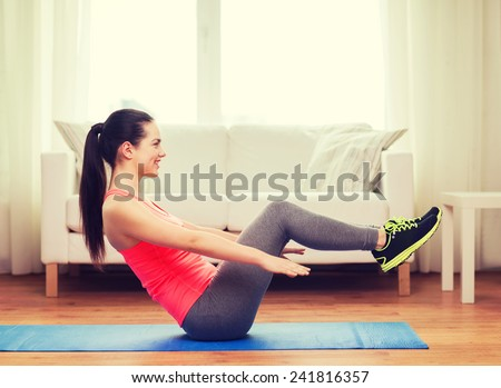fitness, home and diet concept - smiling teenage girl doing exercise on floor at home