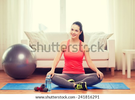 fitness, home and diet concept - smiling teenage girl sitting on mat with sports equipment at home
