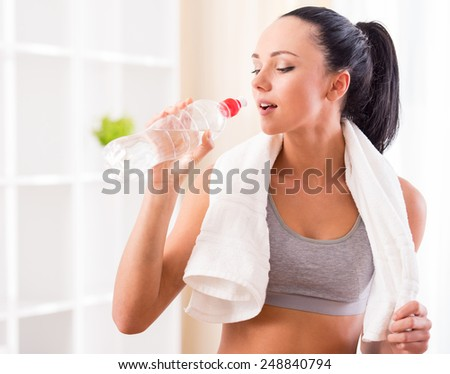 Fitness, home and diet concept. Smiling young woman with bottle of water after exercising at home.