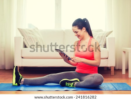 fitness, home, technology and diet concept - smiling teenage girl streching on floor with tablet pc computer at home