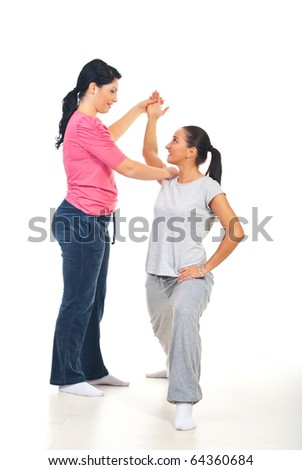 Fitness instructor assisting woman and having conversation together